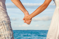 Romantic couple holding hands on beach sunset. During travel. Happy women and men in romance on honeymoon romance in beautiful sun light Royalty Free Stock Image