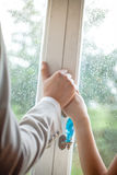 Romantic couple holding hands in front of window with rain drops Stock Image