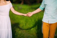 Romantic couple holding hands gently.shadow of them on the grass. Romantic couple holding hands gently. shadow of them on the grass royalty free stock photo
