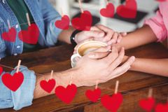 Romantic couple holding hands while having coffee. Mid section of romantic couple holding hands while having coffee Stock Photo