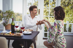 Romantic couple holding hands while having meal Stock Images
