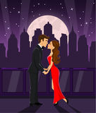 Romantic couple holding hands and kissing. Romantic couple standing on a terrace with night city view, holding hands and kissing Royalty Free Stock Image