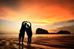 Romantic couple holding hands at sunset on beach Stock Photography