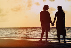 Romantic couple holding hands at sunset beach Royalty Free Stock Photography