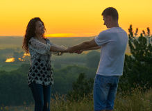 Romantic couple holding hands at sunset on outdoor, beautiful landscape and bright yellow sky, love tenderness concept, young adul Royalty Free Stock Photos
