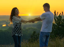 Romantic couple holding hands at sunset on outdoor, beautiful landscape and bright yellow sky, love tenderness concept, young adul Royalty Free Stock Photography