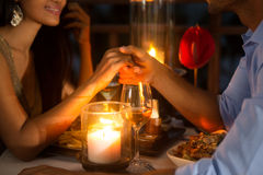 Romantic couple holding hands together over candlelight Stock Images