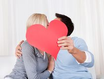 Romantic couple holding a red heart Stock Image