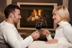 Romantic couple at home. Young romentic couple sitting on sofa in front of fireplace at home, drinking red wine stock photos