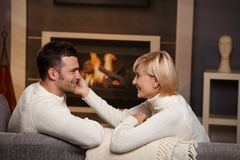 Romantic couple at home. Young romentic couple sitting on sofa in front of fireplace at home, looking at each other, smiling royalty free stock photo