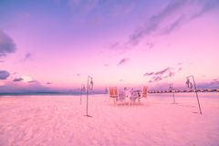 Beach dinner set-up. Sunset sky and chairs and table for romantic couples background royalty free stock photos