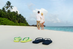 Romantic couple hug on sea sand beach against male and female flip flops Royalty Free Stock Image