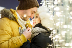 Romantic couple hugging against lights Royalty Free Stock Photography