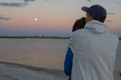 Romantic couple hugging on the beach. And admiring the rising moon. Back view Royalty Free Stock Photography