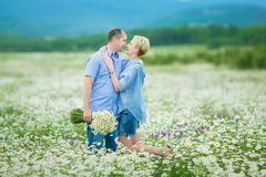 Romantic couple hugging and breathing fresh air in a warm field with daizy flowers. Romantic couple hugging and breathing fresh air in a warm field with daysy royalty free stock photography