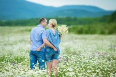 Romantic couple hugging and breathing fresh air in a warm field with daizy flowers. Romantic couple hugging and breathing fresh air in a warm field with daysy stock photos