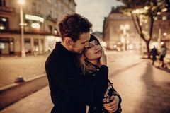 Romantic couple hugging in evening Paris street, handsome bearded man holding beautiful blonde woman in black floral dress. Romantic couple hugging in evening stock photography