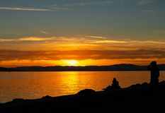 Couple. Sunset. Lake. Color. Silhouette stock image