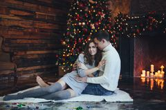 Romantic couple hugging near Christmas tree and fireplace at home in cosy sweaters in the evening stock image