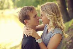 Romantic couple hugging in park. Romantic caucasian couple hugging in park. Young beautiful blonde girl looking at her boyfriend Stock Photo