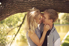 Romantic couple hugging in park. Romantic caucasian couple hugging in park. Young beautiful blonde girl looking at her boyfriend Royalty Free Stock Images