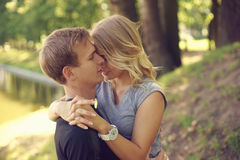 Romantic couple hugging in park. Romantic caucasian couple hugging in park. Young beautiful blonde girl looking at her boyfriend Stock Images