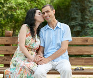 Romantic couple kiss on bench in city park, summer season, adult happy people man and woman Royalty Free Stock Image