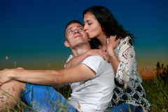 Romantic couple kiss on grass and ebmbrace on country outdoor, dark night sky, love concept, young adult people Royalty Free Stock Photography