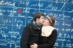 Couple kissing across the I Love You wall Royalty Free Stock Photos