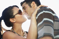 Romantic Couple Kissing Against Sunlight. Closeup of romantic young couple kissing against sunlight Royalty Free Stock Images