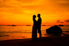Romantic couple kissing at beach with sunset in the bac Stock Images