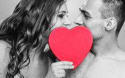 Romantic couple kissing behind red heart Royalty Free Stock Photography