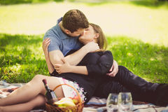 Romantic couple kissing on blanket at park Royalty Free Stock Photography