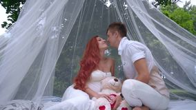 Romantic couple kissing in decorations for wedding photo session at park stock video