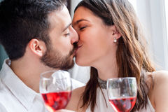 Romantic couple kissing at dinner. Close up face shot of couple kissing at romantic dinner. Out of focus wine glasses in foreground Royalty Free Stock Images