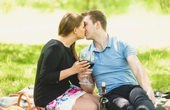 Romantic couple kissing and drinking wine at picnic Stock Photos