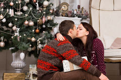 Romantic couple kissing in front of a Xmas tree Stock Photos