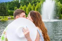 Romantic couple kissing hiding behind the hat Royalty Free Stock Image