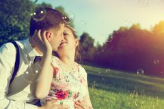 Romantic couple kissing with love in park. Soap bubbles flying stock image