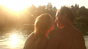 Romantic couple kissing while sitting by the river at sunset stock video
