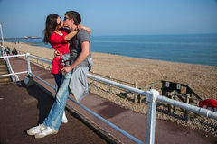 Romantic couple kissing in sunglases on the beach, UK Royalty Free Stock Image