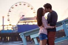 Romantic couple kissing. At sunset in front of santa monica ferris wheel Stock Images