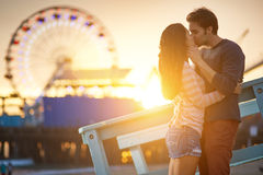 Romantic couple. Kissing at sunset in front of santa monica ferris wheel Stock Photography