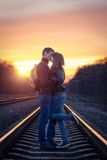 Romantic couple kissing at sunset on railroad Royalty Free Stock Photography