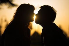 Romantic couple kissing at sunset. Sensual portrait of the profile in silhouette of a romantic couple kissing at sunset with sun flare between their lips Royalty Free Stock Images