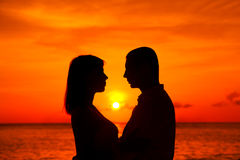 Romantic couple kissing at tropical beach with sunset in the bac Royalty Free Stock Photo