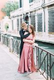 Romantic couple kissing in Venice, Italy. Girl in pink dress and boy in hat and black clothes walking streets of Venice royalty free stock photography