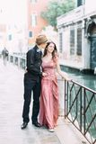 Romantic couple kissing in Venice, Italy. Girl in pink dress and boy in hat and black clothes walking streets of Venice royalty free stock photos