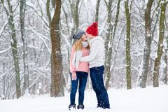 Romantic couple in knitted hats going to kiss during snowfall. Boy and girl in warm sweaters and jeans hug and kiss at winter snow background Stock Photo