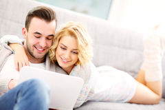 Romantic couple with laptop in living room Stock Photography